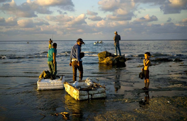 "In this Nov. 11, 2016 photo, young fishermen pull their rafts made out of foam as they head to sea from Chivo Beach in Havana, Cuba. Many Cubans have taken to riding out on blocks of industrial foam to catch larger fish, but the unsafe technique known as ""cork fishing,"" has become the target of frequent coast guard crackdowns with steep fines. (AP Photo/Ramon Espinosa)"