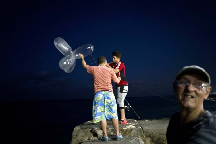 "This Nov. 12, 2016 photo shows Derek Aguiar Gonzalez, a stomatology student and amateur fisherman who said he takes home what he catches, preparing to cast his line, fitted with inflated condoms that serve to keep the bait high in the water and increase the line's resistance against the pull of heavy fish, at the malecon seawall in Havana, Cuba. Few are as creative as what Havana's fishermen call ""balloon fishing,"" a technique employing a couple of cents worth of condoms to pull fish worth an average month's salary from the ocean. (AP Photo/Ramon Espinosa)"