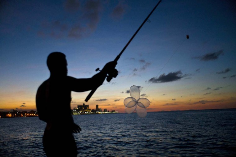 "In this Nov. 13, 2016 photo, mechanic Junior Torres Lopez casts his fishing rod prepared with condoms, known as ""balloon fishing,"" along the Malecon seawall in Havana, Cuba. When the contraceptives are the size of balloons, fishermen tie them together by their ends, attach them to the end of a baited fishing line and set them floating on the tide until they reach the end of the line, as far out as 900-feet. (AP Photo/Ramon Espinosa)"