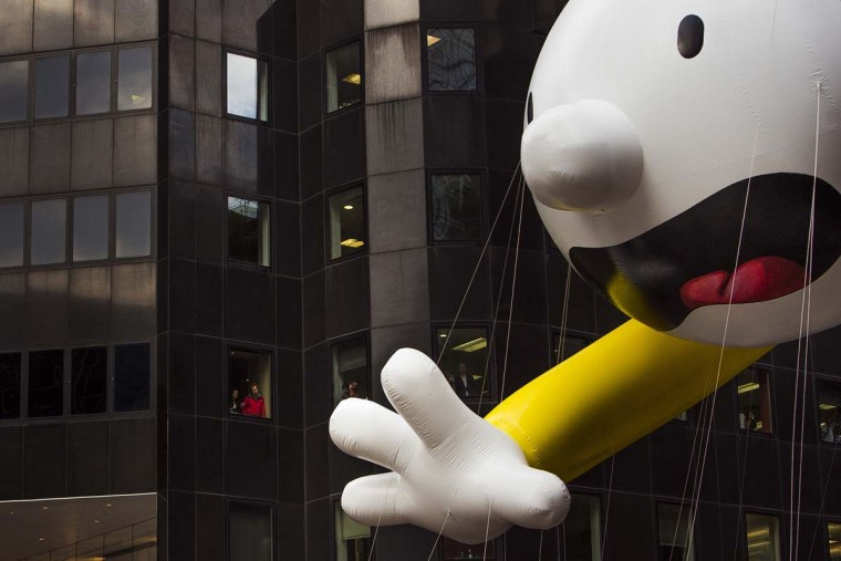 People watch as the Diary of a Wimpy Kid balloon makes its way across Sixth Avenue during the Macy's Thanksgiving Day Parade, in New York, Thursday, Nov. 24, 2016. (AP Photo/Andres Kudacki)