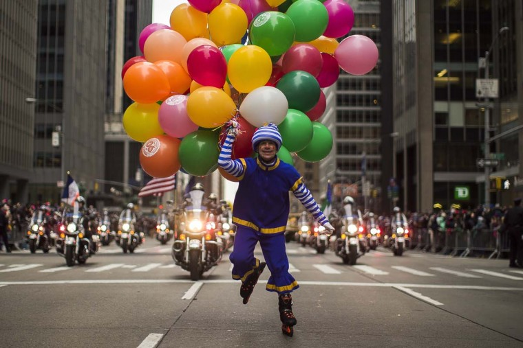 A performer carries balloons across Sixth Avenue during the Macy's Thanksgiving Day Parade, in New York, Thursday, Nov. 24, 2016. (AP Photo/Andres Kudacki)