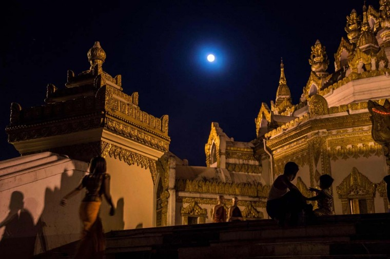 "Buddhist devotees arrive at Swe Taw Myat Pagoda in Yangon under a rising ""supermoon"" on November 14, 2016 as Myanmar celebrates Tazaungdine festival, a mainly religious celebration coinciding with the appearance of super full moon. Skygazers headed to high-rise buildings, ancient forts and beaches on November 14 to witness the closest ""supermoon"" to Earth in almost seven decades, hoping for dramatic photos and spectacular surf. The moon will be the closest to Earth since 1948 at a distance of 356,509 kilometres (221,524 miles), creating what NASA described as ""an extra-supermoon"". (ROMEO GACAD/AFP/Getty Images)"