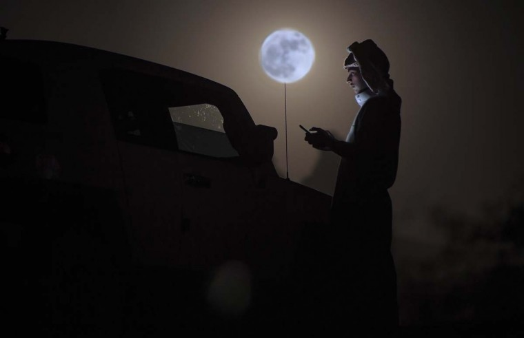 "A man looks at his phone as a ""supermoon"" rises over the desert near Tabuk, some 1500 kilometers northwest of the Saudi capital Riyadh, on November 14, 2016. The phenomenon happens when the moon is full at the same time as, or very near, perigee -- its closest point to Earth on an elliptical, monthly orbit. It was the closest to Earth since 1948 at a distance of 356,509 kilometres (221,524 miles), creating what NASA described as ""an extra-supermoon"". (MOHAMMED ALBUHAISI/AFP/Getty Images)"