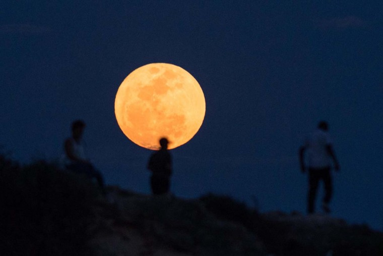 "People watch the supermoon rising in Dar es Salaam on November 14, 2016. The moon will be the closest to Earth since 1948 at a distance of 356,509 kilometres (221,524 miles), creating what NASA described as ""an extra-supermoon"". (DANIEL HAYDUK/AFP/Getty Images)"