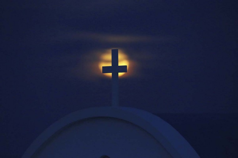 "The moon rises over the Mediterranean sea behind a cross of ""Ayious Saranta"" church in Cape Greco at the eastern part of the island of Cyprus, Monday, Nov. 14, 2016. The brightest moon in almost 69 years, a phenomenon known as the supermoon, is lighting up the sky in a treat for star watchers around the globe. (AP Photo/Petros Karadjias)"