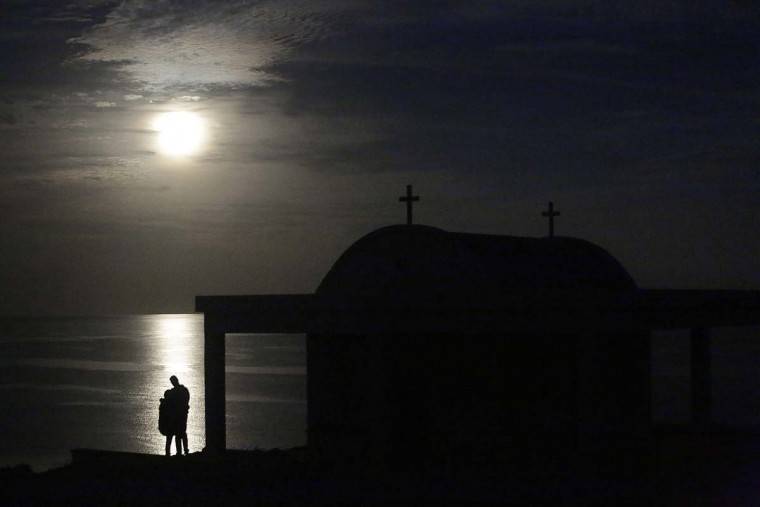 "The moon rises over the Mediterranean sea as a couple stand by the ""Ayious Saranta"" church in Cape Greco at the eastern part of the island of Cyprus, Monday, Nov. 14, 2016. The brightest moon in almost 69 years is lighting up the sky in a treat for star watchers around the globe. (AP Photo/Petros Karadjias)"