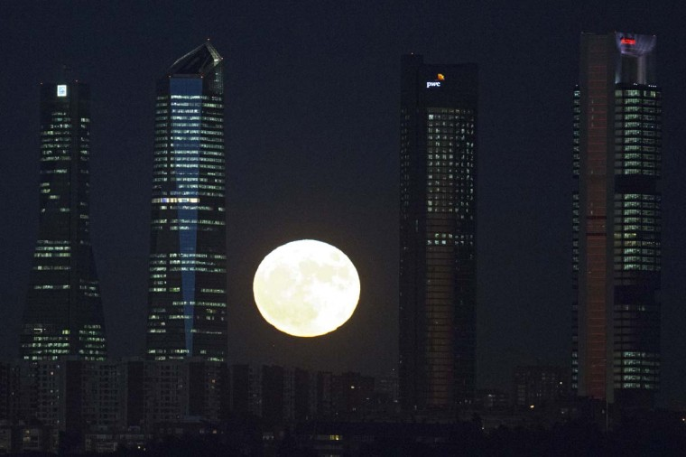 The moon rises behind the four business towers that mark the city skyline in Madrid, Spain, Monday, Nov. 14, 2016. The brightest moon in almost 69 years is lighting up the sky in a treat for star watchers around the globe. (AP Photo/Paul White)
