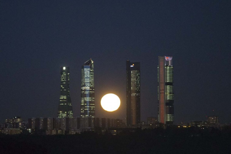 The moon rises behind the four business towers that mark the city skyline in Madrid, Spain, Monday, Nov. 14, 2016. Monday's supermoon is the closest the moon has come to us in almost 69 years. And it won't happen again for another 18 years. (AP Photo/Paul White)