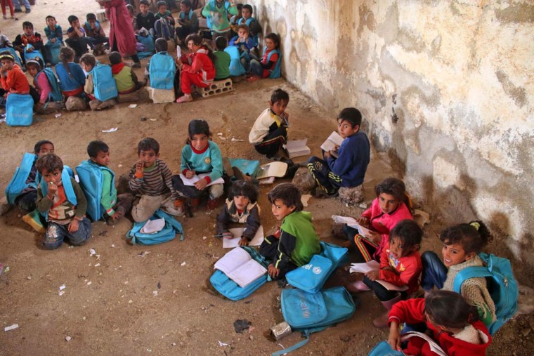 Syrian children sit during class a barn that has been converted into a makeshift school to teach internally displaced children from areas under government control, in a rebel-held area of Daraa, in southern Syria on November 10, 2016. The school has a shortage of seats prompting many children to sit on stones instead. Rebels hold most of Daraa province, but the regional capital is largely controlled by the government. (MOHAMAD ABAZEED/AFP/Getty Images)