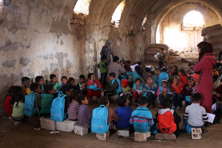 Syrian children write during class a barn that has been converted into a makeshift school to teach internally displaced children from areas under government control, in a rebel-held area of Daraa, in southern Syria on November 10, 2016. The school has a shortage of seats prompting many children to sit on stones instead. Rebels hold most of Daraa province, but the regional capital is largely controlled by the government. (MOHAMAD ABAZEED/AFP/Getty Images)