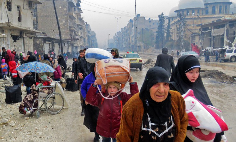 Syrian residents, fleeing violence in the restive Bustan al-Qasr neighbourhood, arrive in Aleppo's Fardos neighbourhood on December 13, 2016, after regime troops retook the area from rebel fighters. Syrian rebels withdrew from six more neighbourhoods in their one-time bastion of east Aleppo in the face of advancing government troops, the Syrian Observatory for Human Rights said. (STRINGER/AFP/Getty Images)