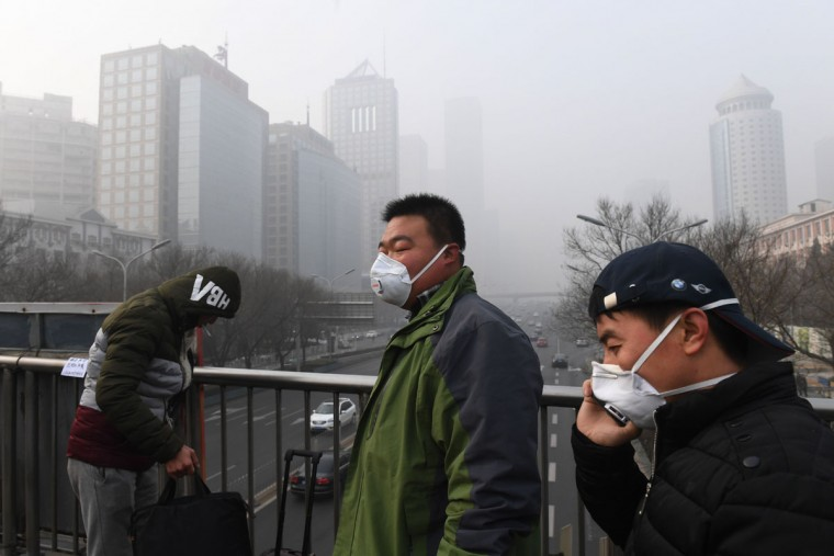 Pedestrians wear masks on a polluted day in Beijing on December 20, 2016. Heavy smog suffocated northeast China for a fifth day on December 20, with hundreds of flights cancelled and road and rail transport grinding to a halt under the low visibility conditions. (AFP PHOTO / Greg Baker)