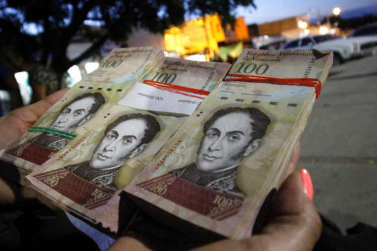 "A woman shows wads of 100-bolivar-bills to change in La Parada, municipality of Villa del Rosario, Norte de Santander department, Colombia, in the border with Venezuela, on December 11, 2016. Venezuelan President Nicolas Maduro on Sunday signed an emergency decree ordering the country's largest banknote, the 100 bolivar bill, taken out of circulation to thwart ""mafias"" he accused of hoarding cash in Colombia. (AFP PHOTO / SCHNEYDER MENDOZA)"