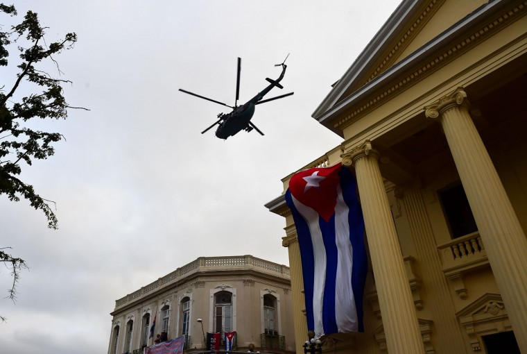 A helicopter overflies Santa Clara, Cuba, on December 1, 2016 as the urn with the ashes of Cuban leader Fidel Castro is driven through the city during its four-day journey across the island for the burial in Santiago de Cuba. A military jeep is taking the ashes of Fidel Castro on a four-day journey across Cuba, with islanders lining the roads to bid farewell to the late communist icon. Castro died at 90 on November 25, 2016 and will be buried in the eastern city of Santiago de Cuba on Sunday. (Ronaldo Schemidt/AFP/Getty Images)