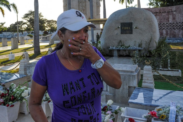 A woman places flowers in the tomb of former Cuban President Fidel Castro at the Cementerio Santa Ifigenia, on December 4, 2016 in Santiago de Cuba. Fidel Castro's ashes were buried alongside national heroes in the cradle of his revolution, as Cuba opens a new era without the communist leader who ruled the island for decades. (Yamil Lage/AFP/Getty Images)