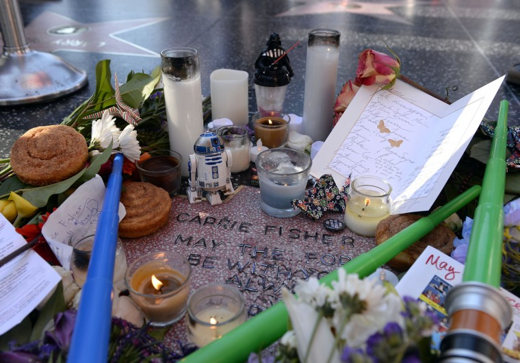 "Carrie Fisher is remembered with a makeshift star on the Hollywood Walk of Fame December 29, 2016 in Hollywood, California. The star was reportedly made by a fan who added Fisher's name to a blank star along with the words ""may the force be with you always"" and ""hope."" Fisher was never nominated for a star while living and now won't be eligible until the fifth anniversary of her death. (Photo by Kevork Djansezian/Getty Images)"