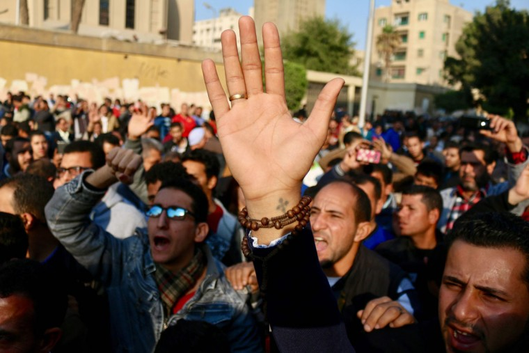 Egyptians shout slogans as they gather outside the the Saint Peter and Saint Paul Coptic Orthodox Church in Cairo's Abbasiya neighbourhood after it was targeted by a bomb explosion on December 11, 2016, . The blast killed at least 25 worshippers during Sunday mass inside the Cairo church near the seat of the Coptic pope who heads Egypt's Christian minority, state media said. (AFP PHOTO / MOHAMED METEAB)