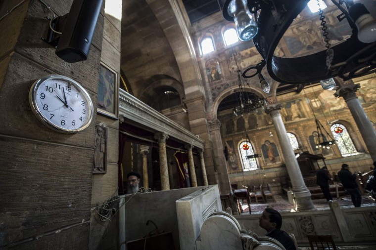 Egyptian security forces and members of the clergy inspect the scene of a bomb explosion at the Saint Peter and Saint Paul Coptic Orthodox Church on December 11, 2016, in Cairo's Abbasiya neighbourhood. The blast killed at least 25 worshippers during Sunday mass inside the Cairo church near the seat of the Coptic pope who heads Egypt's Christian minority, state media said. (AFP PHOTO / KHALED DESOUKI)