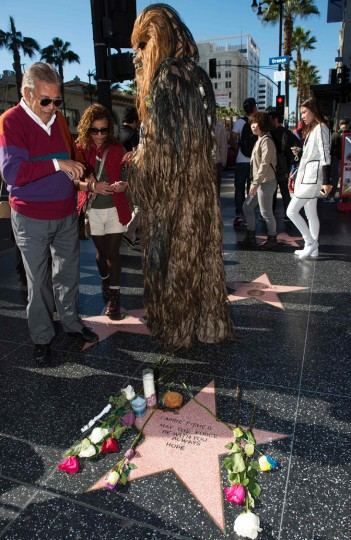 "People stop by to view a temporary star made by fans in tribute to actress Carrie Fisher on Hollywood Walk of Fame in Hollywood, California, on December 28, 2016. Friends, fans and Hollywood stars added their voices to a torrent of tributes for ""Star Wars"" actress Carrie Fisher, who died Tuesday at the age of 60 following a heart attack. (Valerie Macon/AFP/Getty Images)"