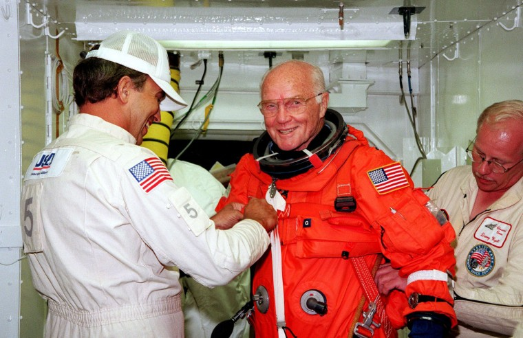 FILE - This file photo taken on October 9, 1998 shows US astronaut and Senator John Glenn getting a hand from white room technicians moments before boarding the US space shuttle Discovery. Glenn, who made history twice as the first American to orbit the Earth and the first senior citizen to venture into space, has died at the age of 95, the Ohio State University's John Glenn College of Public Affairs said on December 8, 2016. (NASA/HOHO/AFP/Getty Images)