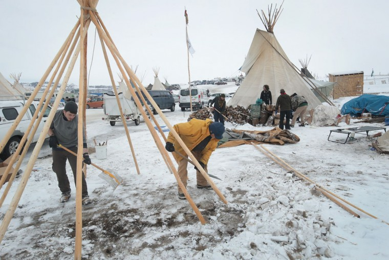 Jameson Dargen (L) of Fargo, North Dakota and Peter Anderson of Fairfax, California build a tipi at Oceti Sakowin Camp on the edge of the Standing Rock Sioux Reservation on December 2, 2016 outside Cannon Ball, North Dakota. Native Americans and activists from around the country have been gathering at the camp for several months trying to halt the construction of the Dakota Access Pipeline. The proposed 1,172-mile-long pipeline would transport oil from the North Dakota Bakken region through South Dakota, Iowa and into Illinois. (Photo by Scott Olson/Getty Images)