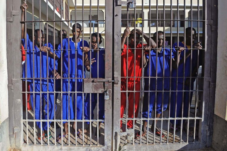 Somali prisoners convicted of piracy, stand behind a gate of the prison in Garowe, Puntland state, in northeastern Somalia, on December 14, 2016. The prison facilitates the rehabilitation of convicted Somali pirates and suspected Al-Shabaab jihadists. (MOHAMED ABDIWAHAB/AFP/Getty Images)