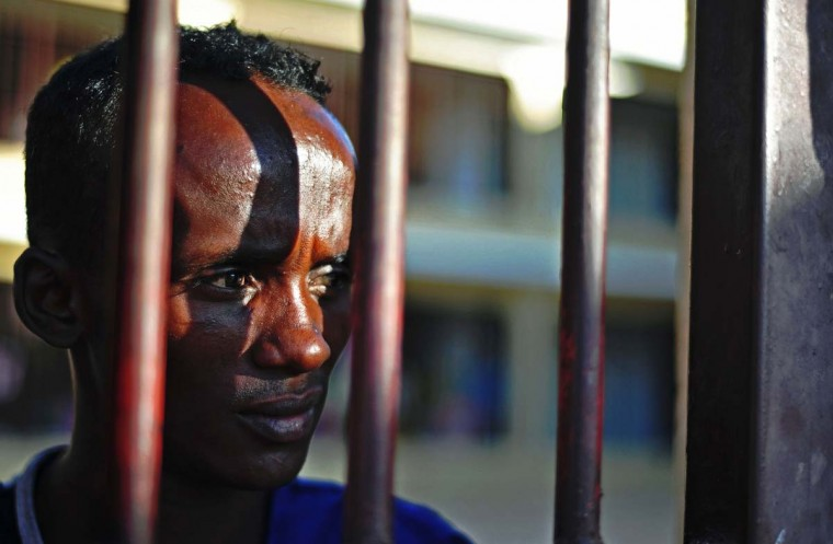 A prisoner looks through bars, at the prison in Garowe, Puntland state, in northeastern Somalia, on December 14, 2016. The prison facilitates the rehabilitation of convicted Somali pirates and suspected Al-Shabaab jihadists. (MOHAMED ABDIWAHAB/AFP/Getty Images)