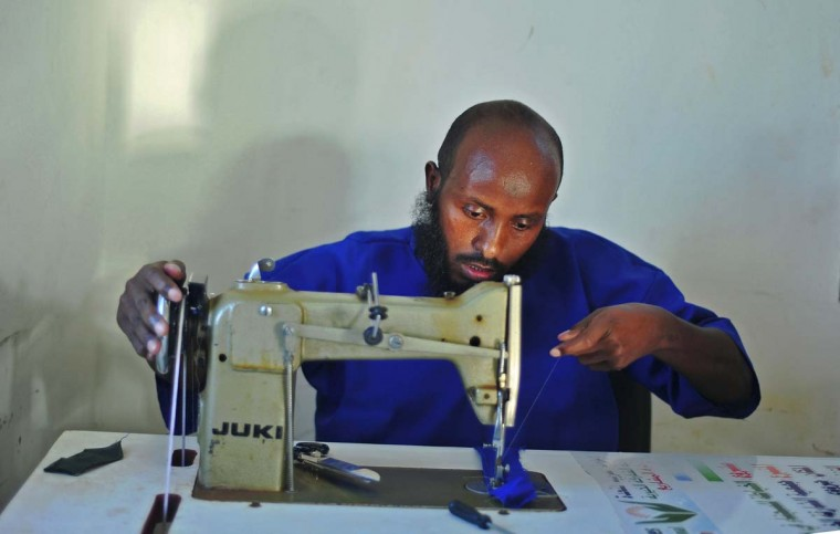 A prisoner sews at a prison in Garowe, Puntland state, in northeastern Somalia, on December 14, 2016. The prison facilitates the rehabilitation of convicted Somali pirates and suspected Al-Shabaab jihadists. (MOHAMED ABDIWAHAB/AFP/Getty Images)