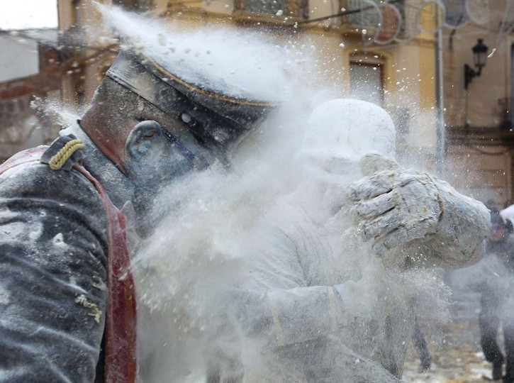 "Revellers dressed in mock military garb take part in the ""Enfarinats"" battle in the southeastern Spanish town of Ibi on December 28, 2016. During this 200-year-old traditional festival participants known as Els Enfarinats (those covered in flour) dress in military clothes and stage a mock coup d'etat as they battle using flour, eggs and firecrackers outside the city town hall as part of the celebrations of the Day of the Innocents. (JAIME REINAJAIME REINA/AFP/Getty Images)"