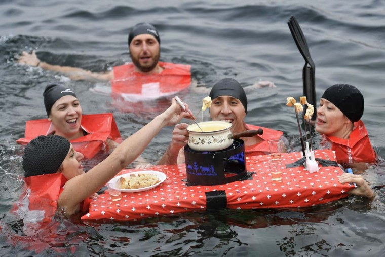 "People eat a cheese fondue as they swim during the 78th ""Coupe de Noel"" (Christmas cup) swimming race in the Lake Geneva, on December 18, 2016 in Geneva. More than 1800 participants took part in the event, a 12-meter-long swimming off the Geneva's bank in the 7 degrees Celsius cold water. (FABRICE COFFRINI/AFP/Getty Images)"