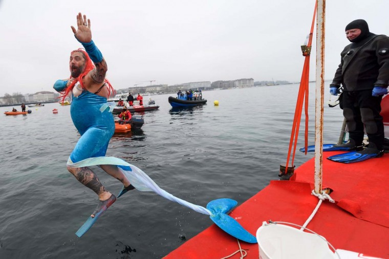 "A man disguised as a mermaid jumps into the water during the 78th ""Coupe de Noel"" (Christmas cup) swimming race in the Lake Geneva, on December 18, 2016 in Geneva. More than 1800 participants took part in the event, a 12-meter-long swimming off the Geneva's bank in the 7 degrees Celsius cold water. (FABRICE COFFRINI/AFP/Getty Images)"
