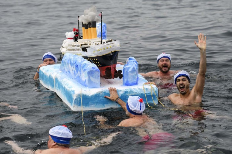 "Participants swim with a model of the Titanic ship during the 78th ""Coupe de Noel"" (Christmas cup) swimming race in the Lake Geneva, on December 18, 2016 in Geneva. More than 1800 participants took part in the event, a 12-meter-long swimming off the Geneva's bank in the 7 degrees Celsius cold water. (FABRICE COFFRINI/AFP/Getty Images)"