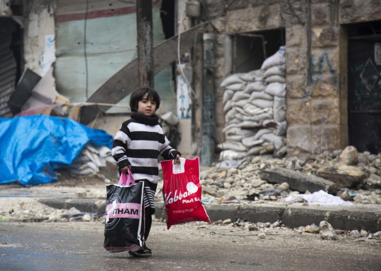 A Syrian boy is seen among other civilains leaving a rebel-held area of Aleppo towards the government-held side on December 13, 2016 during an operation by Syrian government forces to retake the embattled city. UN chief Ban Ki-moon expressed alarm over reports of atrocities against civilians Monday, as the battle for Aleppo entered its final phase with Syrian government forces on the verge of retaking rebel-held areas of the city. (AFP PHOTO / KARAM AL-MASRI)
