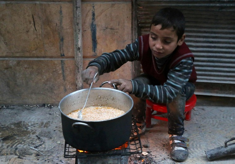 A Syrian child cooks in the street in a rebel-held area of Aleppo, on December 13, 2016, during an operation by Syrian government forces to retake the embattled city. UN chief Ban Ki-moon expressed alarm over reports of atrocities against civilians Monday, as the battle for Aleppo entered its final phase with Syrian government forces on the verge of retaking rebel-held areas of the city. (STRINGER PHOTO/AFP/Getty Images)