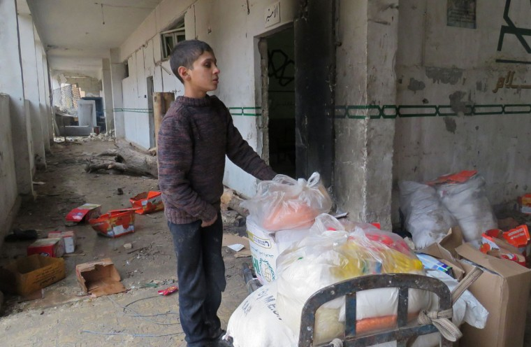 A Syrian boy takes food from a storage room that was formerly held by the opposition forces in eastern Aleppo's al-Kalasseh neighbourhood on December 13, 2016, after pro-government forces captured the area. (AFP PHOTO / STRINGER)