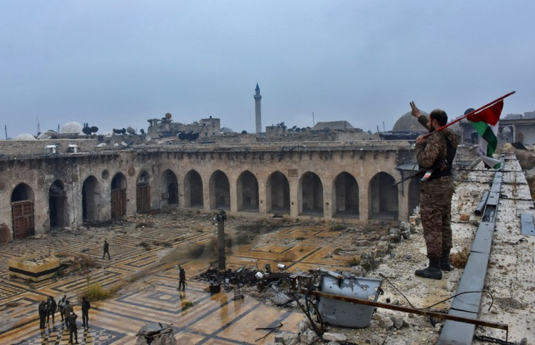 A general view shows a member of the Syrian pro-government forces holding a Palestinian flag and flashing the sign for victory as he stands on the roof og the ancient Umayyad mosque in the old city of Aleppo on December 13, 2016, after they captured the area. After weeks of heavy fighting, regime forces were poised to take full control of Aleppo, dealing the biggest blow to Syria's rebellion in more than five years of civil war. (AFP PHOTO / George OURFALIAN)