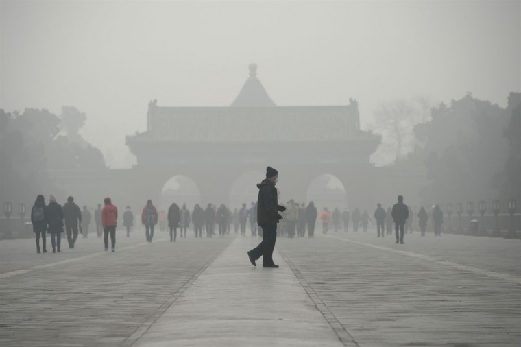 An elderly man walks in front of a group of people during heavy smog at a the Temple of Heaven park in Beijing on December 20, 2016. Heavy smog suffocated northeast China for a fifth day on December 20, with hundreds of flights cancelled and road and rail transport grinding to a halt under the low visibility conditions. (AFP PHOTO/WANG ZHAO)