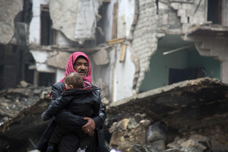 Syrians leave a rebel-held area of Aleppo towards the government-held side on December 13, 2016 during an operation by Syrian government forces to retake the embattled city. UN chief Ban Ki-moon expressed alarm over reports of atrocities against civilians Monday, as the battle for Aleppo entered its final phase with Syrian government forces on the verge of retaking rebel-held areas of the city. (AFP PHOTO / KARAM AL-MASRI)