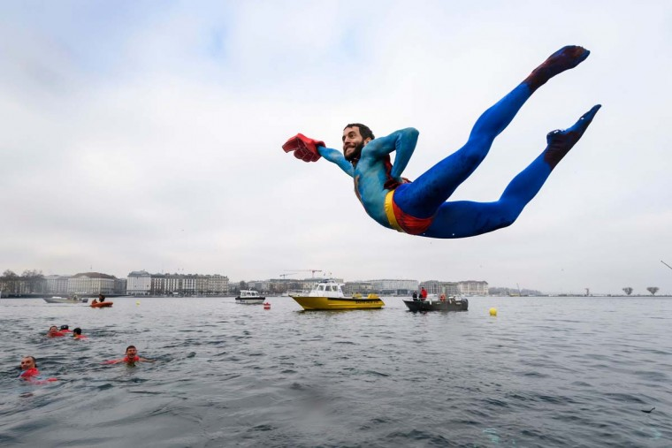 "A swimmer disguised as Superman dives into the lake during the 78th ""Coupe de Noel"" (Christmas cup) swimming race in the Lake Geneva, on December 18, 2016 in Geneva. More than 1800 participants took part in the event, a 12-meter-long swimming off the Geneva's bank in the 7 degrees Celsius cold water. (FABRICE COFFRINI/AFP/Getty Images)"