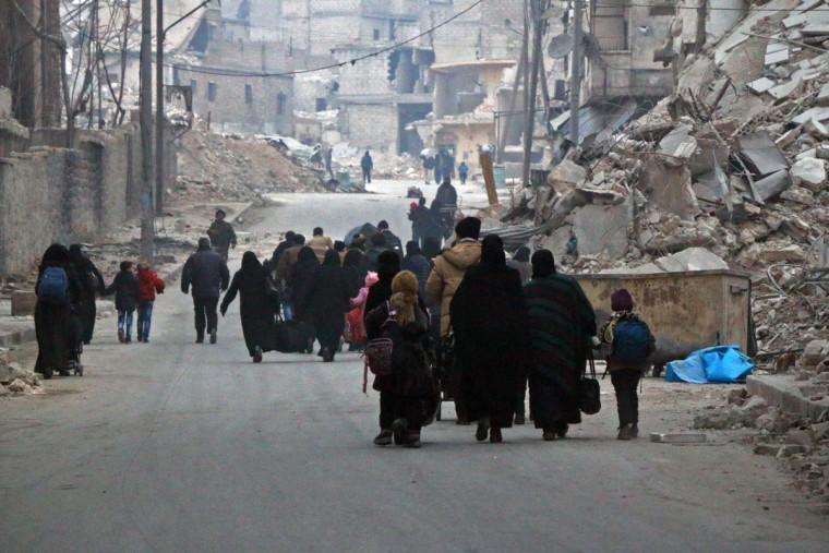 "Syrian civilians flee the Sukkari neighbourhood towards safer rebel-held areas in southeastern Aleppo, on December 12, 2016, during an operation by Syrian government forces to retake the embattled city. The crucial battle for Aleppo entered its ""final phase"" after Syrian rebels retreated into a small pocket of their former bastion in the face of new army advances. The retreat leaves opposition fighters confined to just a handful of neighbourhoods in southeast Aleppo, the largest of them Sukkari and Mashhad. (AFP PHOTO / STRINGER)"