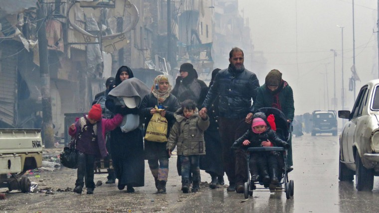 Syrian residents, fleeing violence in the restive Bustan al-Qasr neighbourhood, arrive in Aleppo's Fardos neighbourhood on December 13, 2016, after regime troops retook the area from rebel fighters. Syrian rebels withdrew from six more neighbourhoods in their one-time bastion of east Aleppo in the face of advancing government troops, the Syrian Observatory for Human Rights said. (AFP PHOTO /STRINGER)