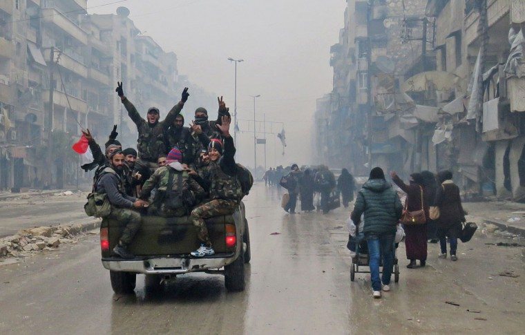 Syrian pro-regime fighters, gesture as they drive past residents fleeing violence in the restive Bustan al-Qasr neighbourhood, in Aleppo's Fardos neighbourhood on December 13, 2016, after regime troops retook the area from rebel fighters. Syrian rebels withdrew from six more neighbourhoods in their one-time bastion of east Aleppo in the face of advancing government troops, the Syrian Observatory for Human Rights said. (AFP PHOTO / STRINGER)