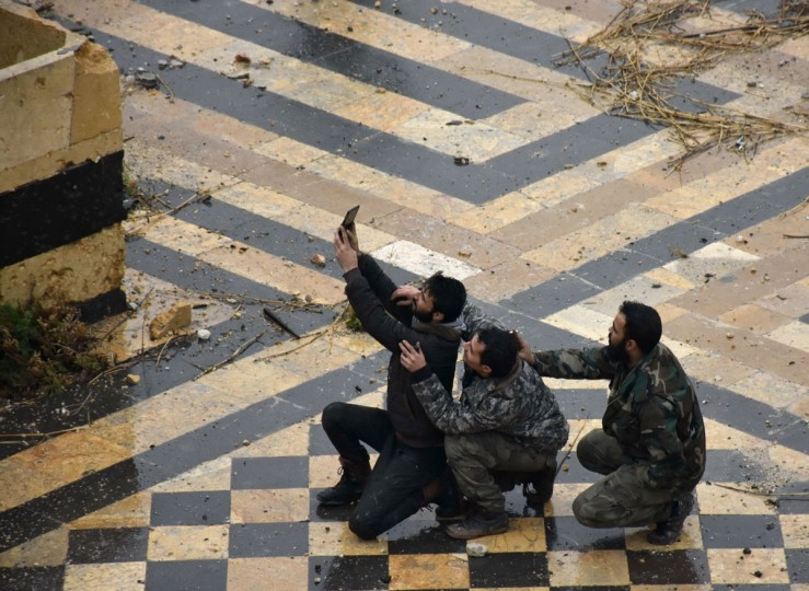 Syrian pro-government forces take a selfie in the courtyard of the ancient Umayyad mosque in the old city of Aleppo on December 13, 2016. After weeks of heavy fighting, regime forces were poised to take full control of Aleppo, dealing the biggest blow to Syria's rebellion in more than five years of civil war. (AFP PHOTO / George OURFALIAN)