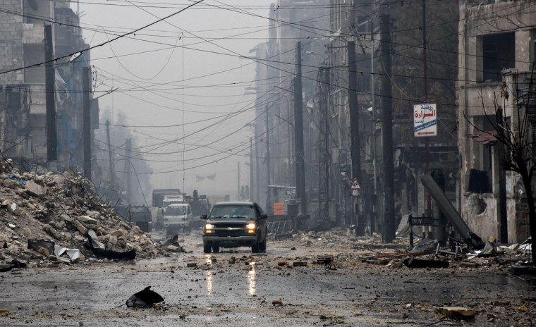 A general view shows pro-government forces driving along a severely damaged street in Aleppo's newly captured Al-Kalasseh neighbourhood in the eastern part of the war torn city on December 13, 2016. After weeks of heavy fighting, regime forces were poised to take full control of Aleppo, dealing the biggest blow to Syria's rebellion in more than five years of civil war. (AFP PHOTO / George OURFALIAN)