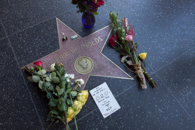"Flowers adorn one of the Hollywood Walk of Fame stars for actress Debbie Reynolds on December 29, 2016, in Hollywood, California. Reynolds, the ""Singin' in the Rain"" actress who tap-danced her way into American hearts as a star of Hollywood's Golden Age, died on December 28, 2016, grief-stricken over daughter Carrie Fisher's death a day earlier. (David McNew/AFP/Getty Images)"