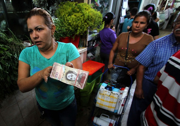 "A woman shows a wad of 100-Bolivar-bills in San Cristobal, Venezuela on December 12, 2016. Venezuelan President Nicolas Maduro on Sunday signed an emergency decree ordering the country's largest banknote, the 100 bolivar bill, taken out of circulation to thwart ""mafias"" he accused of hoarding cash in Colombia. (AFP PHOTO / GEORGE CASTELLANOS)"