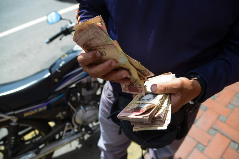 "A man counts 100-Bolivar-bills on the street in Caracas on December 12, 2016. Venezuelan President Nicolas Maduro on Sunday signed an emergency decree ordering the country's largest banknote, the 100 bolivar bill, taken out of circulation to thwart ""mafias"" he accused of hoarding cash in Colombia. (AFP PHOTO / FEDERICO PARRA)"