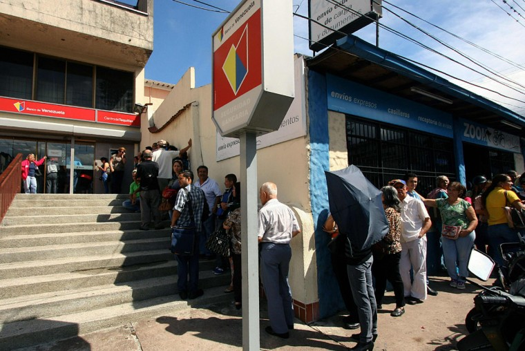 "People queue to use ATMs in San Cristobal, Venezuela on December 12, 2016. Venezuelan President Nicolas Maduro on Sunday signed an emergency decree ordering the country's largest banknote, the 100 bolivar bill, taken out of circulation to thwart ""mafias"" he accused of hoarding cash in Colombia. (AFP PHOTO / GEORGE CASTELLANOS)"
