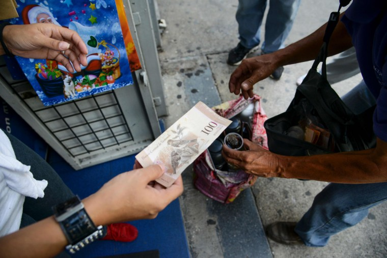 "A woman a coffee to a peddler with a 100-bolivar-bill in Caracas on December 12, 2016. Venezuelan President Nicolas Maduro on Sunday signed an emergency decree ordering the country's largest banknote, the 100 bolivar bill, taken out of circulation to thwart ""mafias"" he accused of hoarding cash in Colombia. (AFP PHOTO / Federico PARRA)"