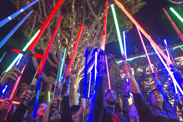 "Fans of actress Carrie Fisher honored her death by pointing their lit ""Star Wars"" light sabers to the sky at 7 p.m. at Downtown Disney, Wednesday night, Dec. 28, 2016, in Anaheim. (Mark Eades/The Orange County Register via AP)"